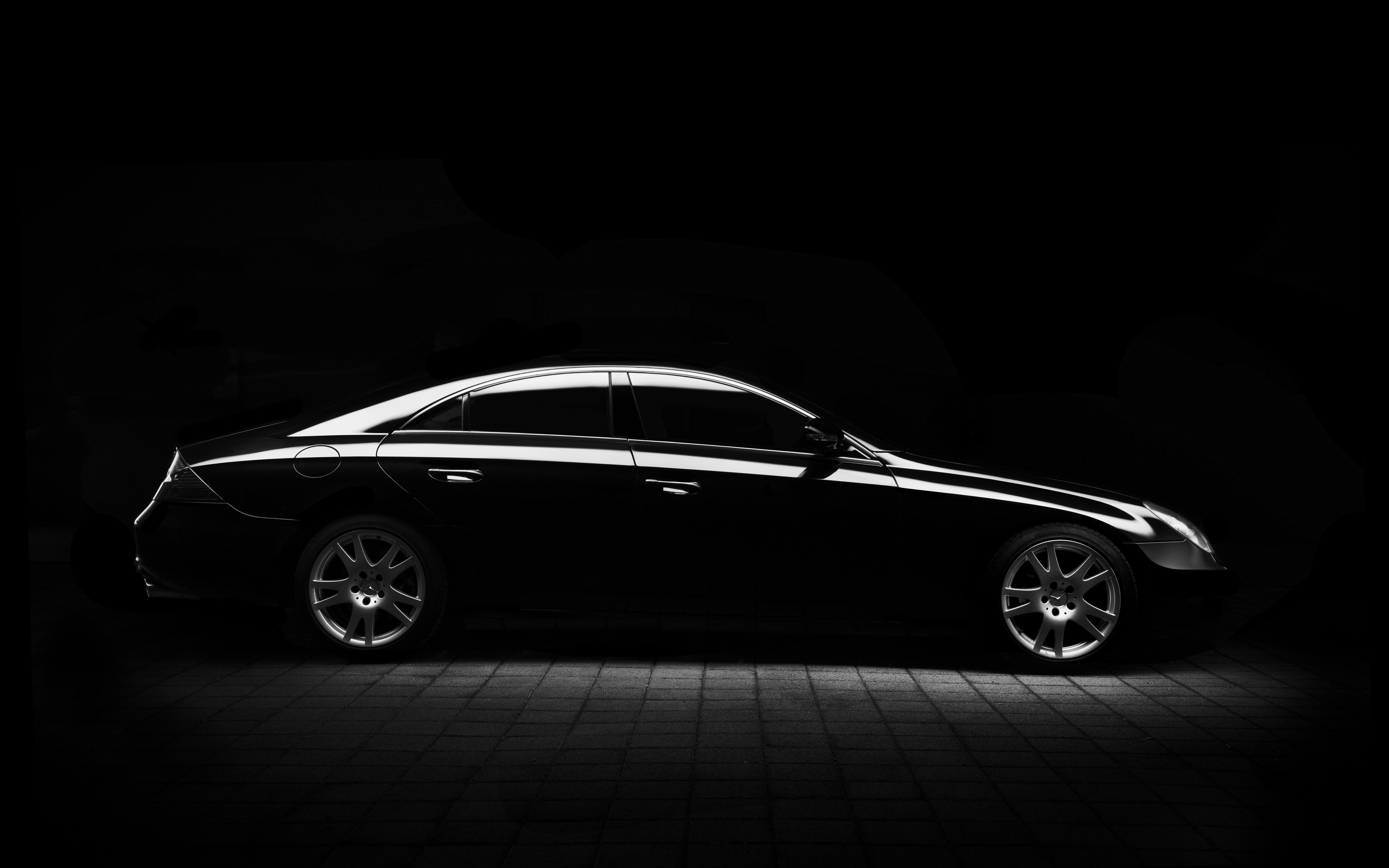 Black and white shot of black Mercedes-Benz saloon car on pavement at night
