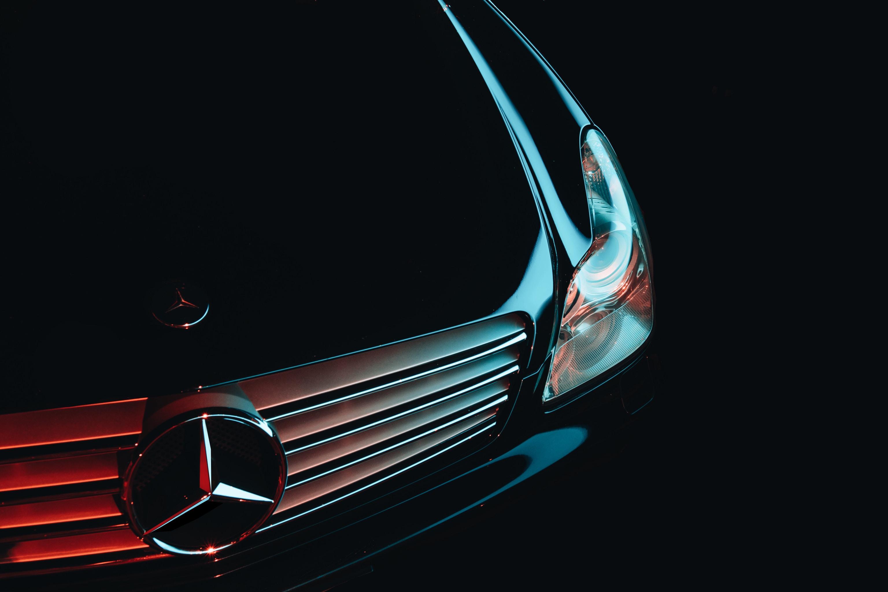 Hood ornament and front bumper details on a black Mercedes Benz