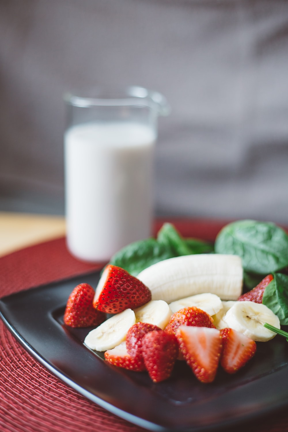 sliced strawberries and bananas on black plate beside white liquid-filled clear drinking glass