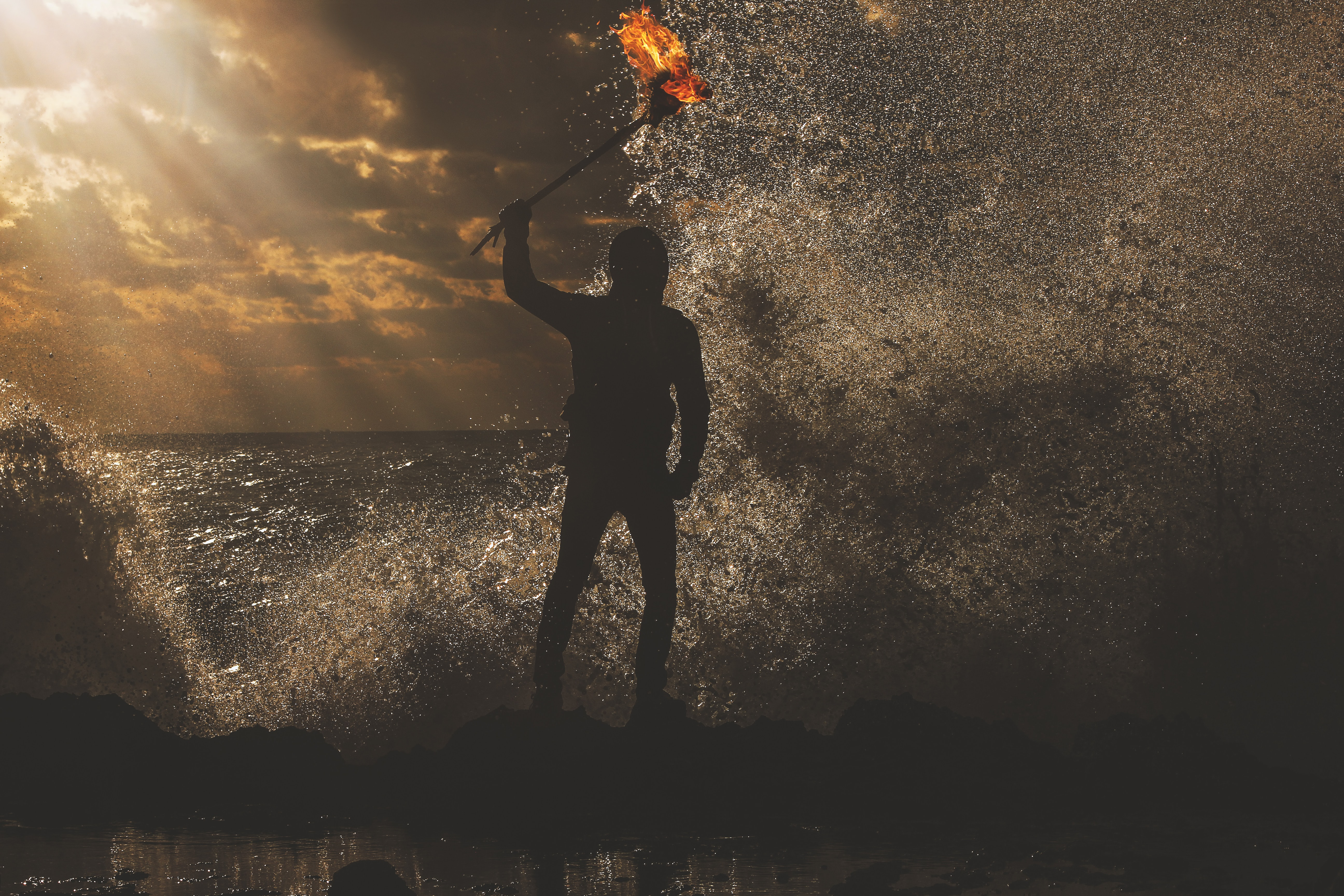 A man standing in the water during sunset at dusk, while holding a torch.