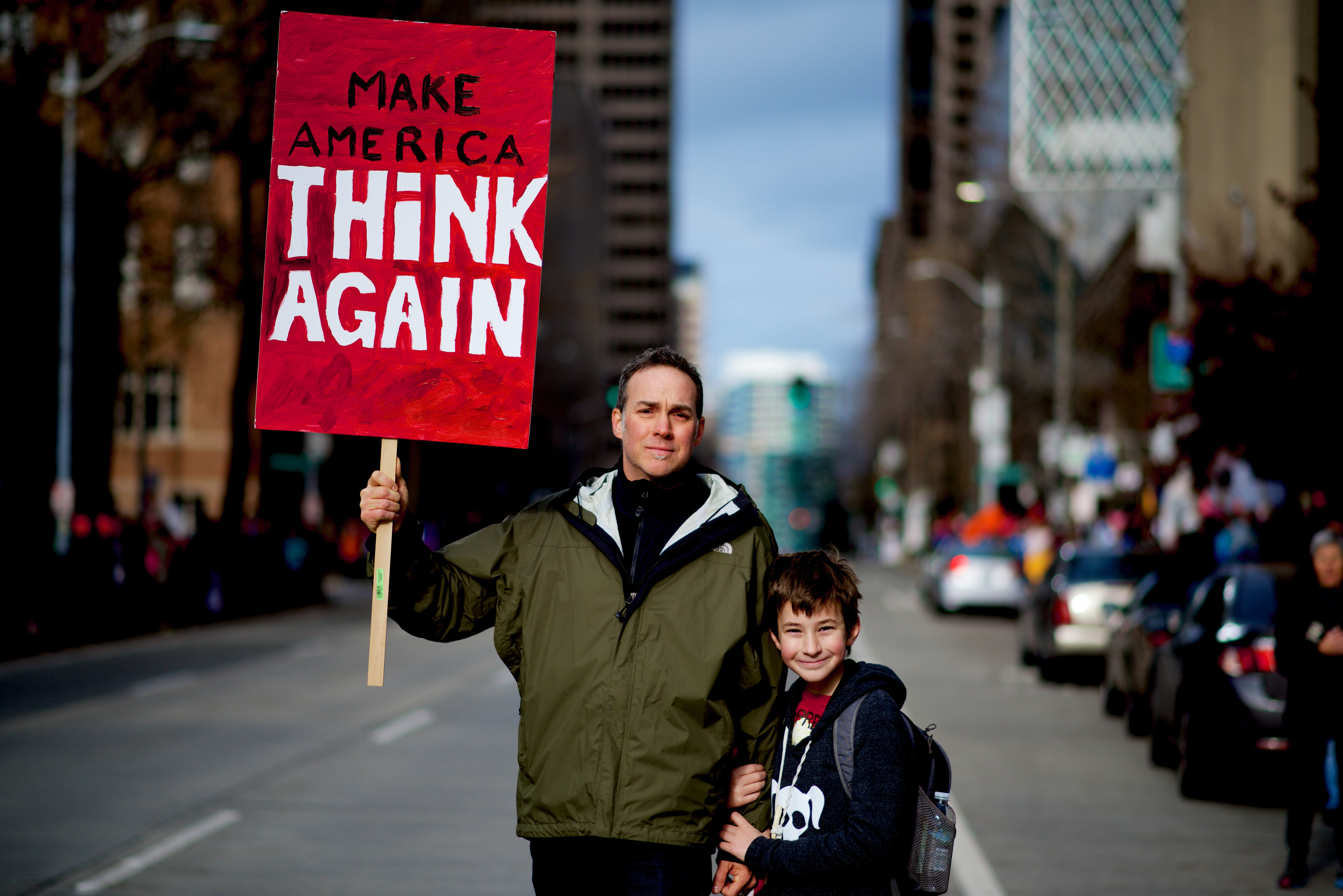 """Amid city streetsm a father holds up a sign reading """"Make America Think Again"""" as his son holds his hand"""