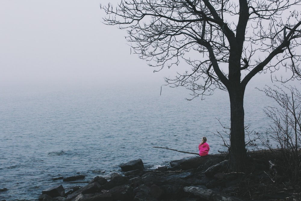 person wearing pink dress sitting near ocean