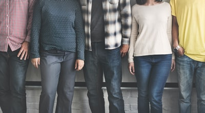 low-angle photography of five person wearing blue and black denim jeans