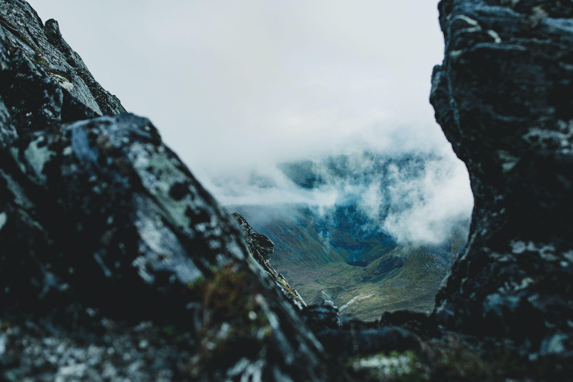 Peeking through mountains at a misty valley below