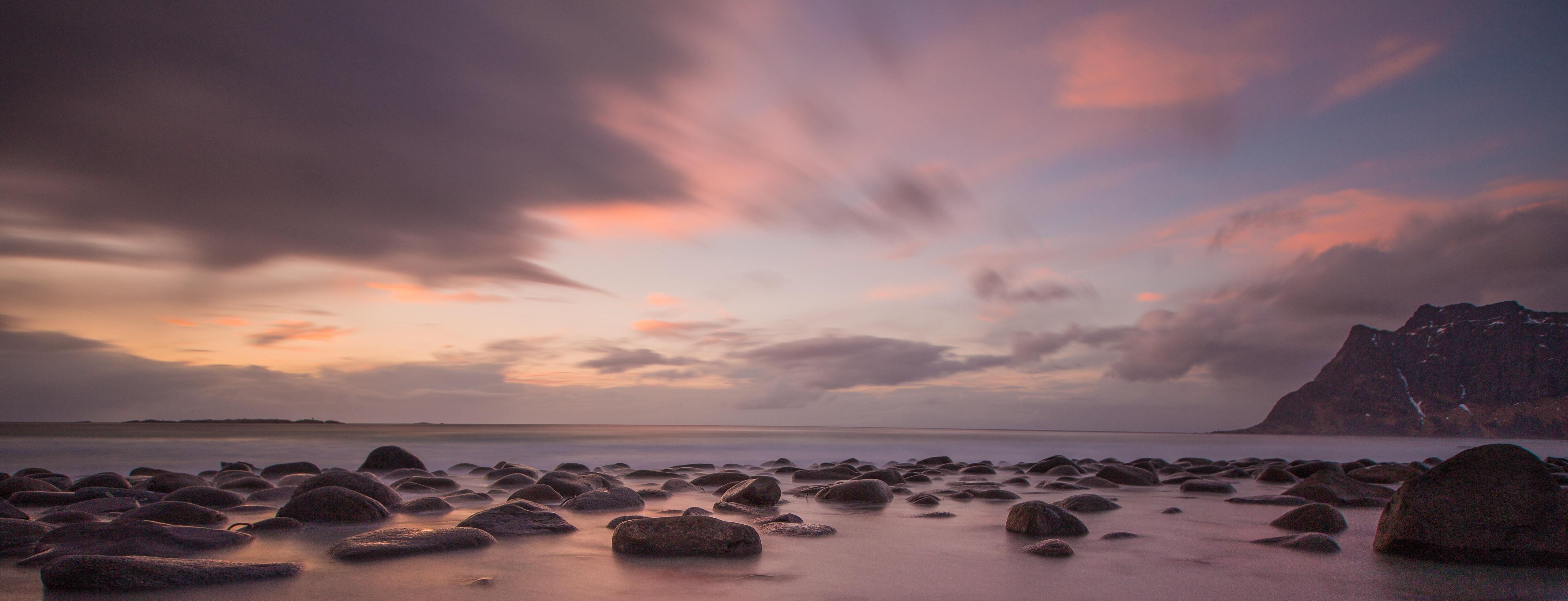 rock formation near shoreline during golden hour