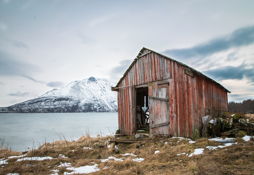 landscape photography of brown wooden shed near ocean water and snow-coated mountains during daytime