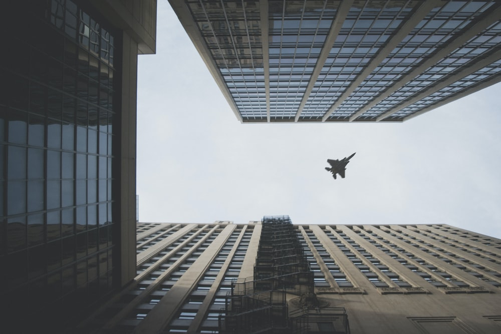 worm's view photo of fighter jet flying above building