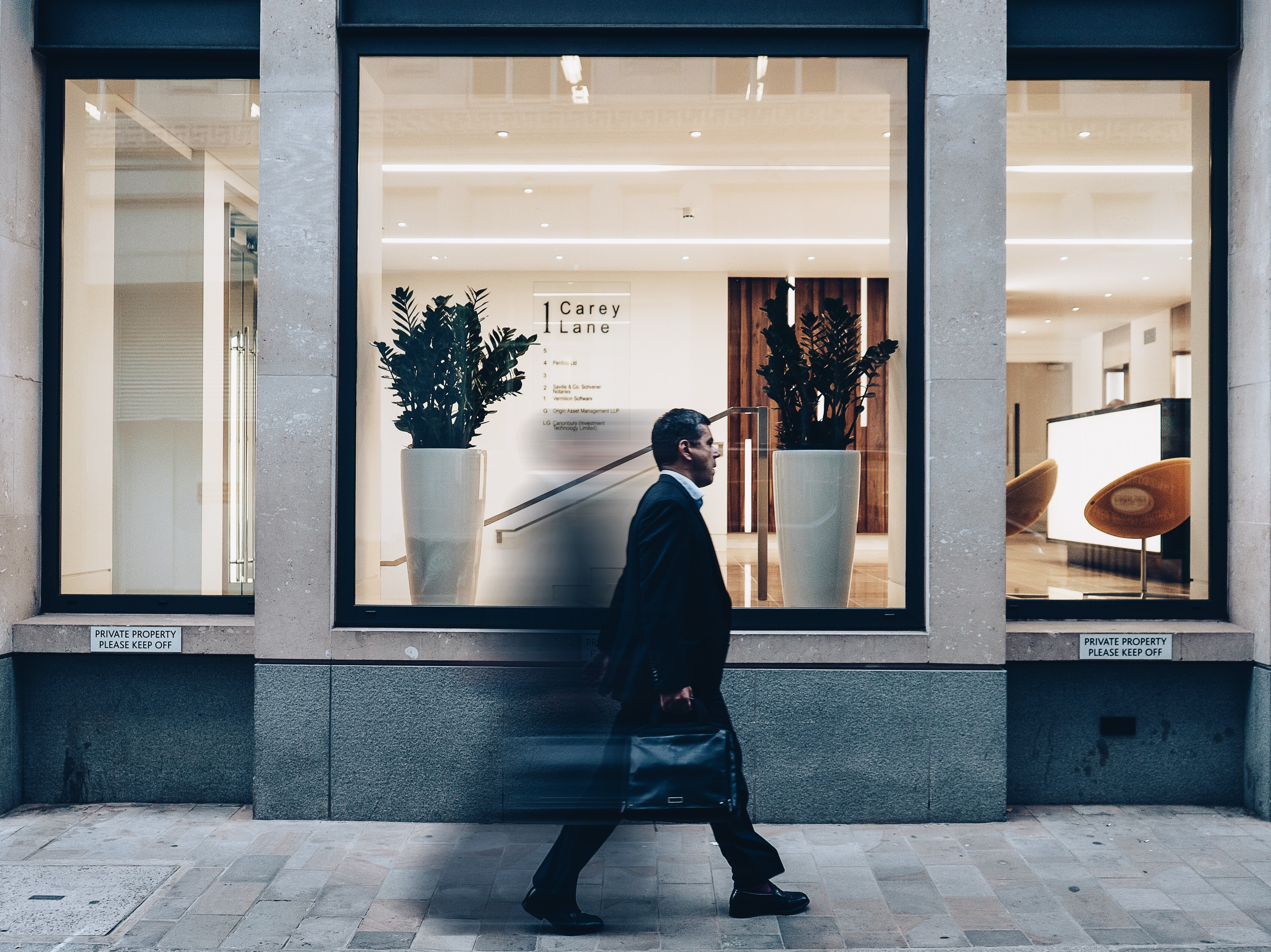 A man in a suit with a suitcase walking past an office building in London