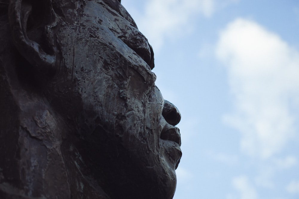 person statue under white clouds closeup photography
