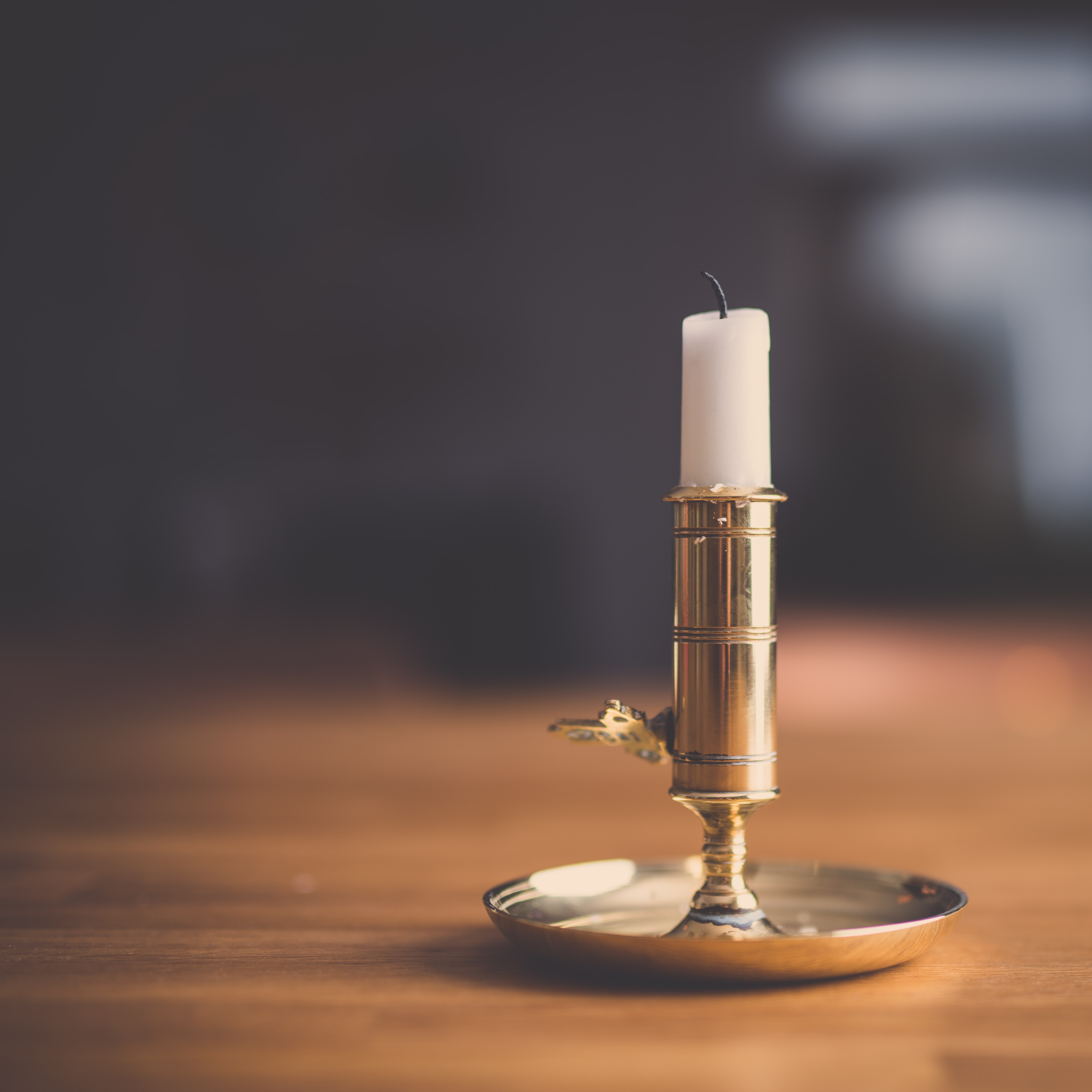 A macro shot of a white candle in a gold candle holder