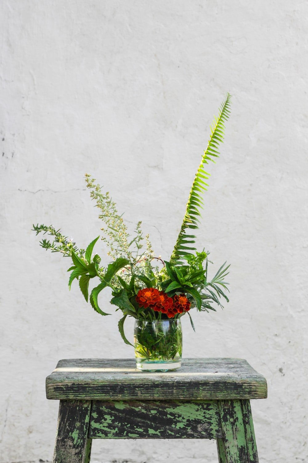 red petaled flowers in glass vase on blue wooden bar stool