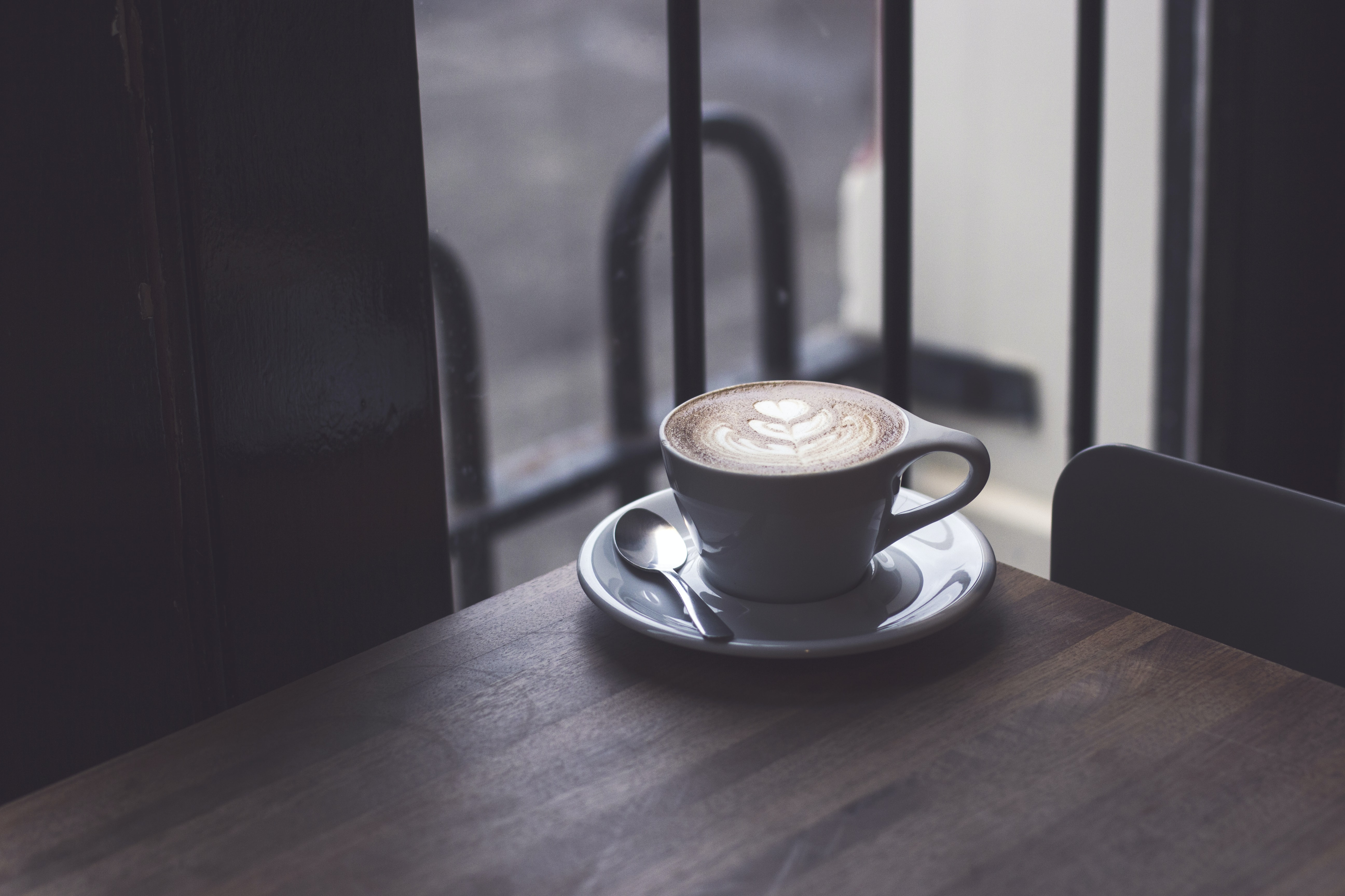 Cup of espresso on a plate on the corner of a brown, wood table in front of a glass window