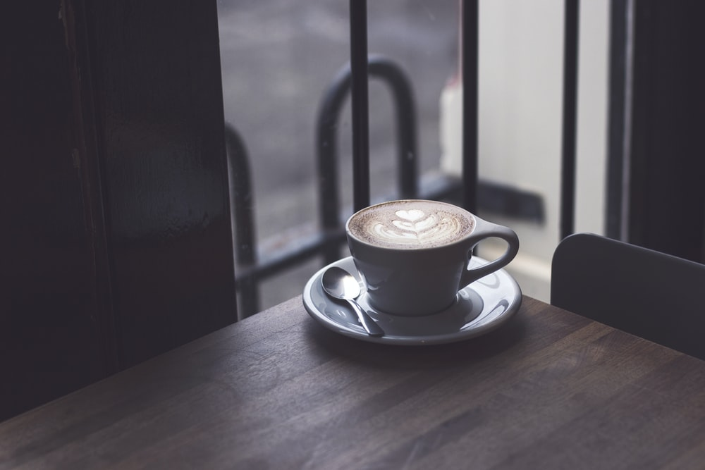 cappuccino in white teacup on brown wooden surface