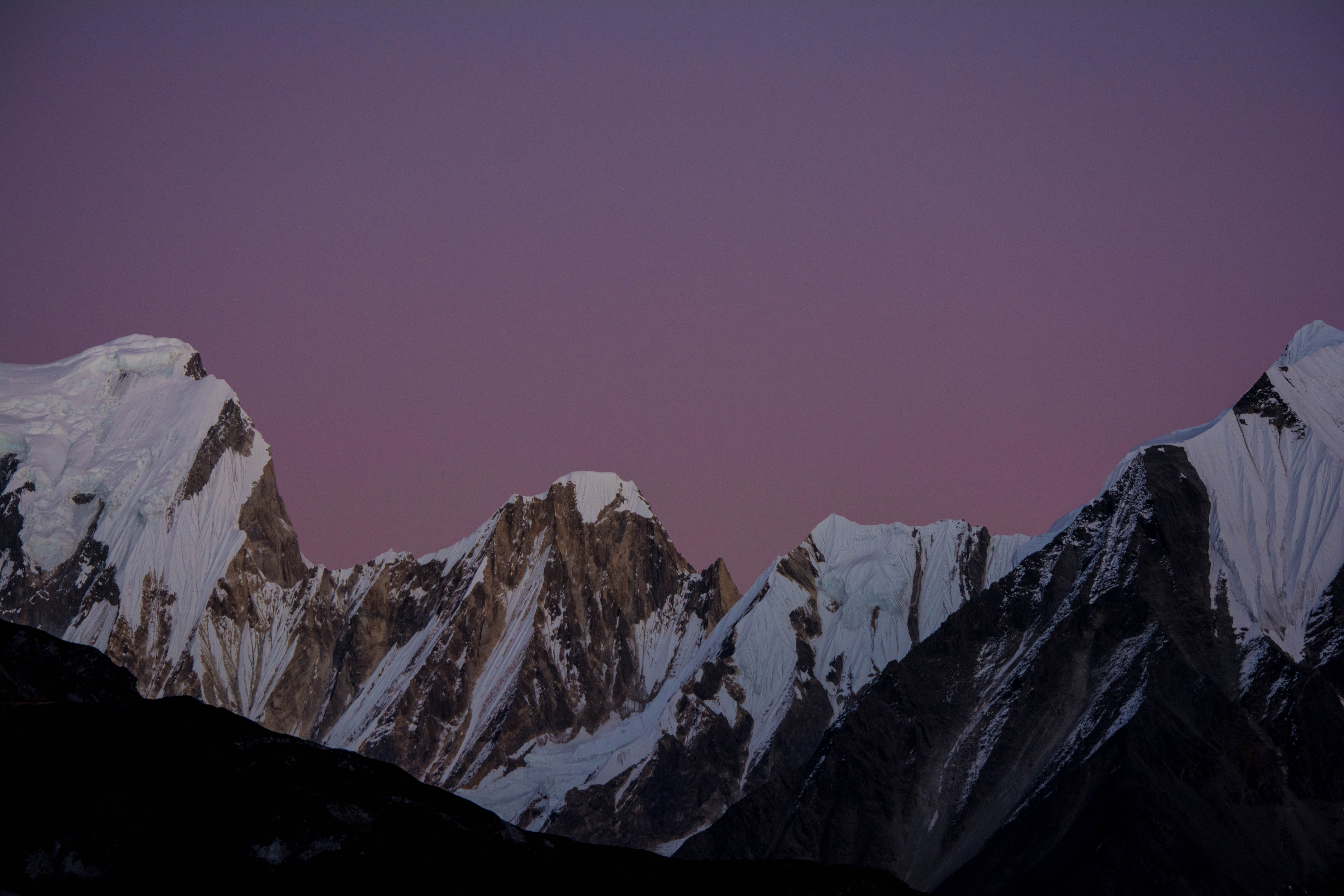 Purple evening sky over snow-capped mountains