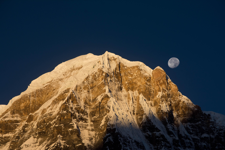 Waning moon on the dark blue sky over a sharp mountain ridge