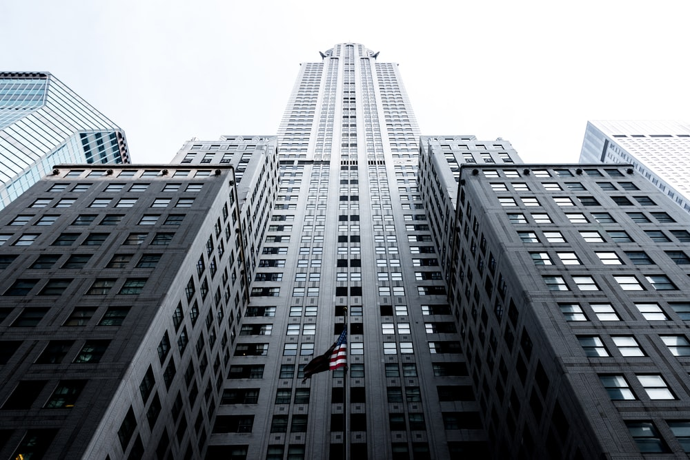 low angle photo of gray concrete high-rise building