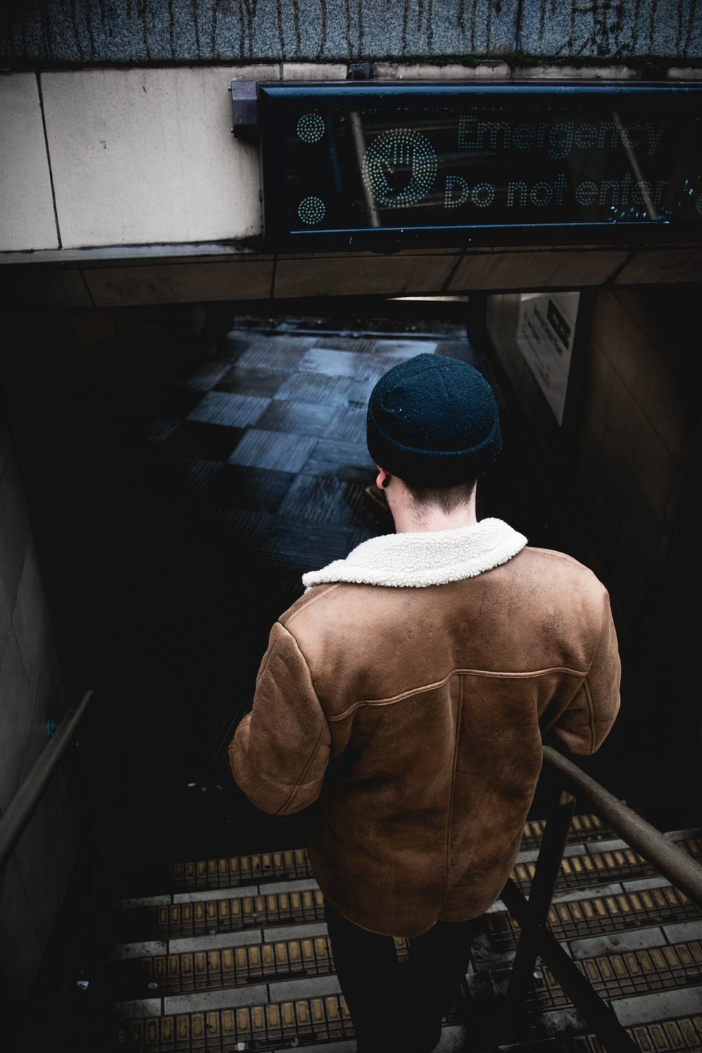 person in brown jacket walking on the stair