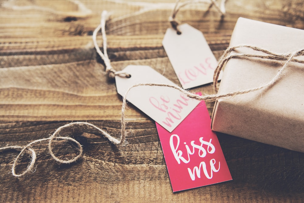 "Paper tags with ""kiss me"" written on one of them next to a wrapped gift"