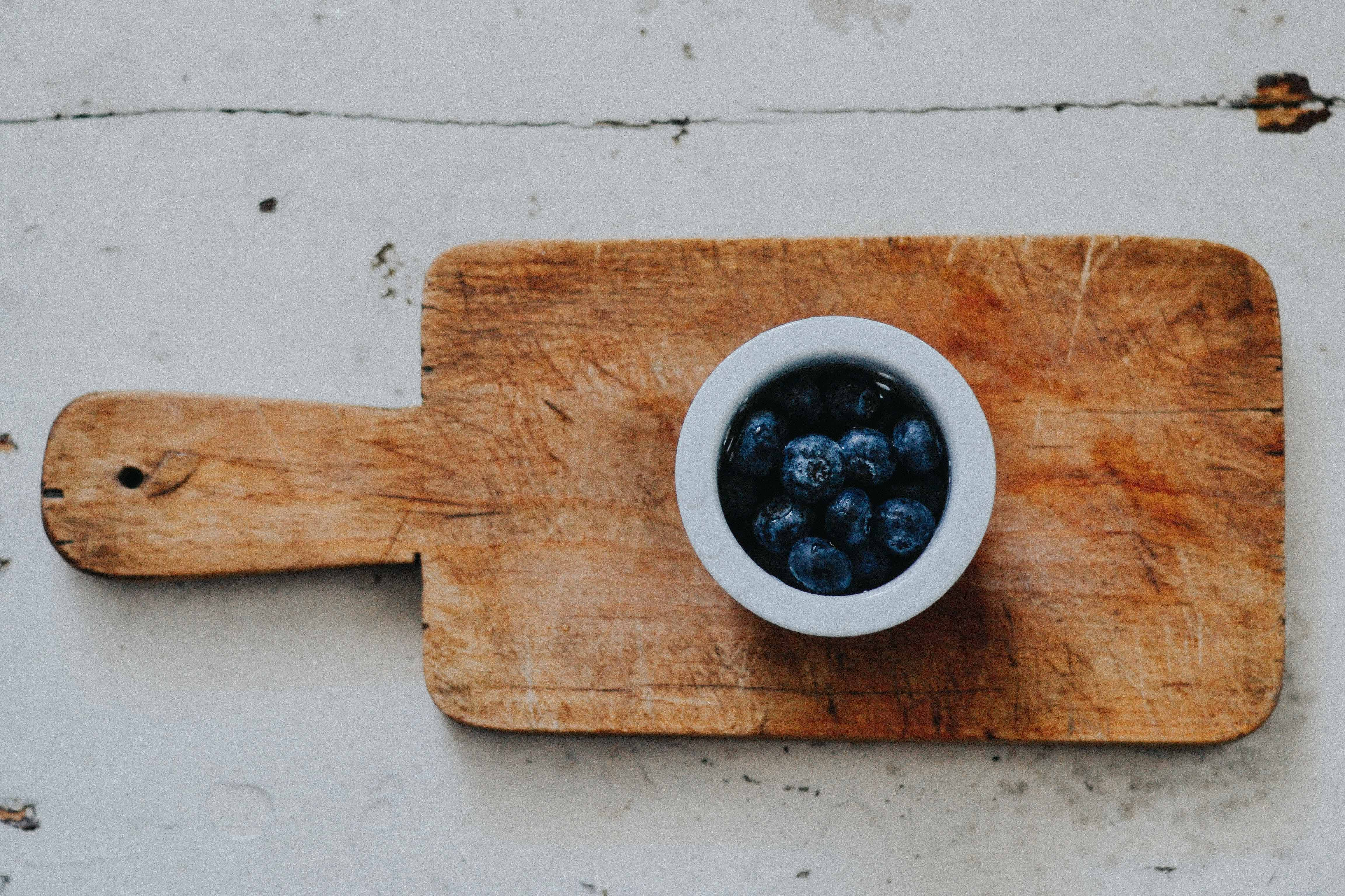 White cup of blueberries on top of cutting board on top of wooden surface