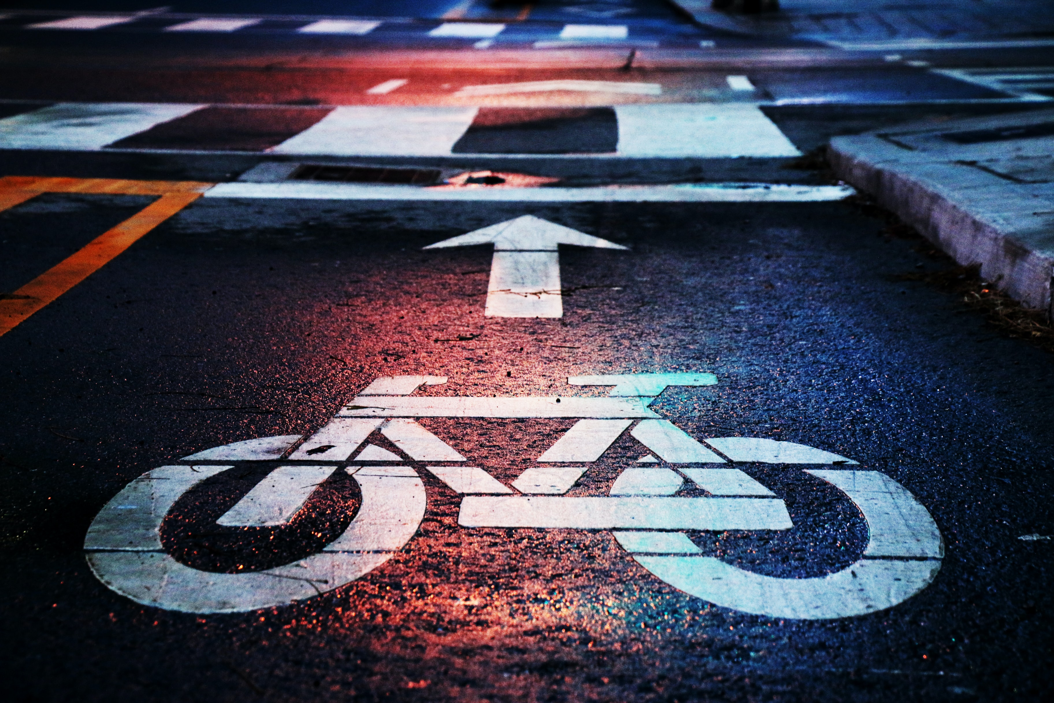 Macro of white bike lane markings on a street at night near a crosswalk
