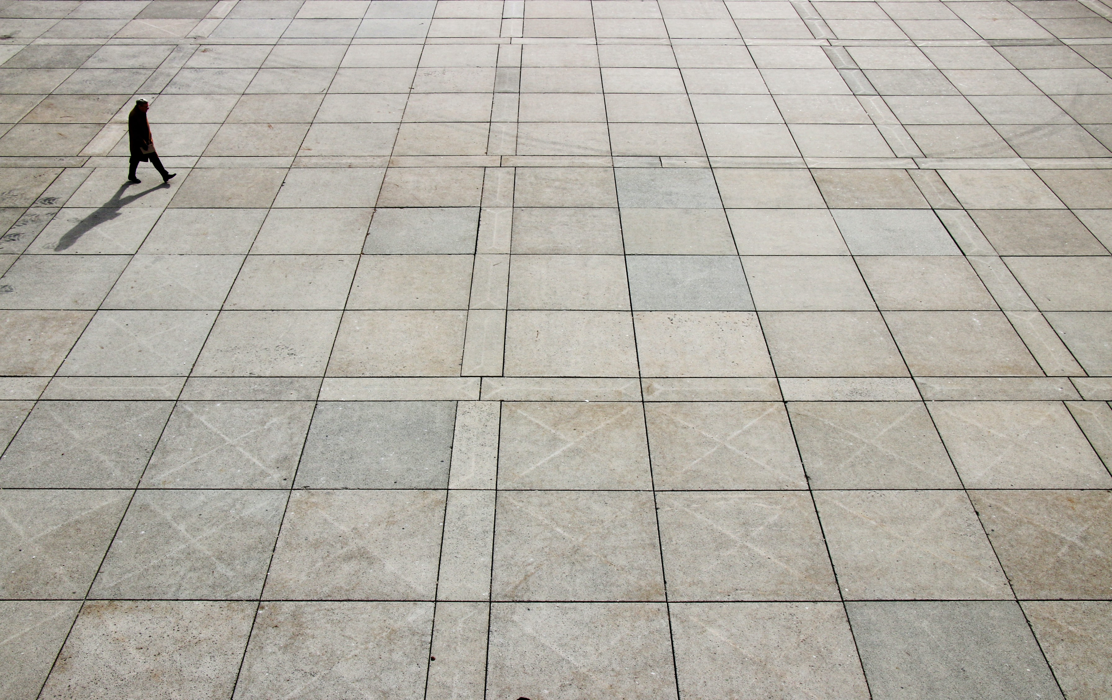 A high shot of a lone person walking across a large plaza