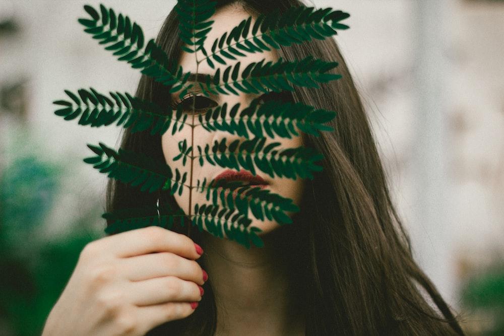girl holding leaf outdoor during daytime