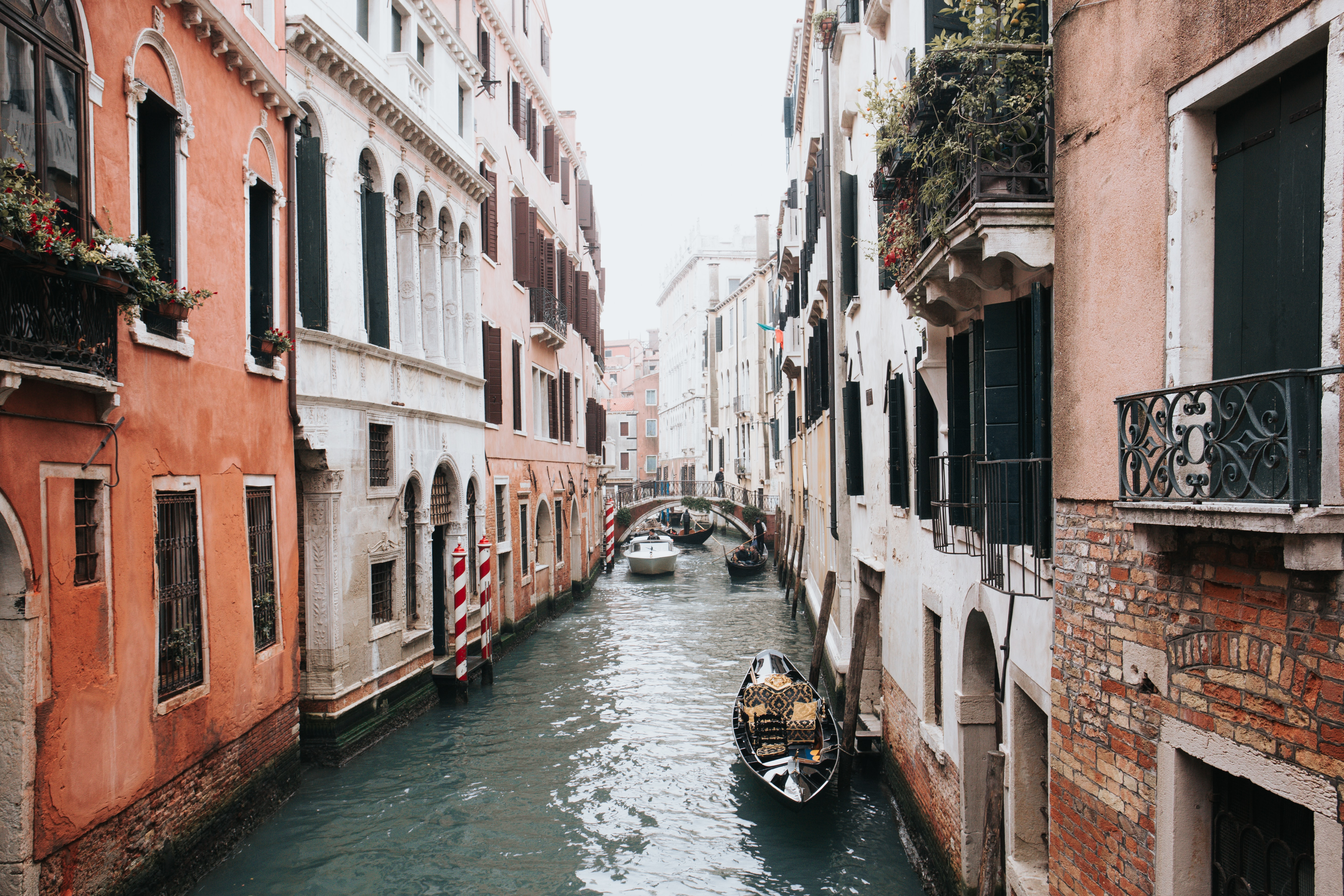 A canal in Venice with a gondola in front and a bridge in the back