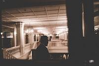 man standing inside higher floor of building near stairs