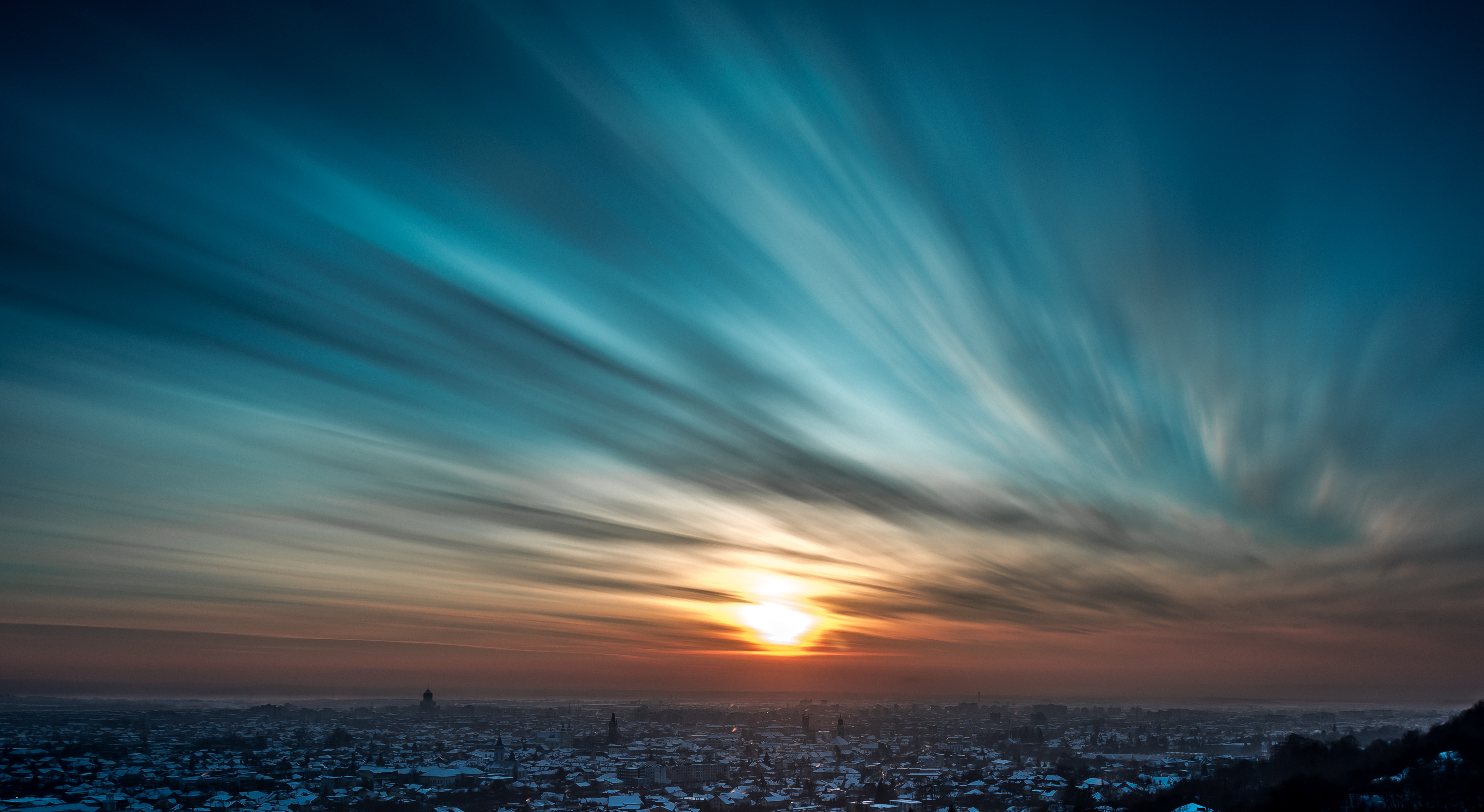 A long exposure shot of the clouds and sky at sunset over the city of Baia Mare, Romania