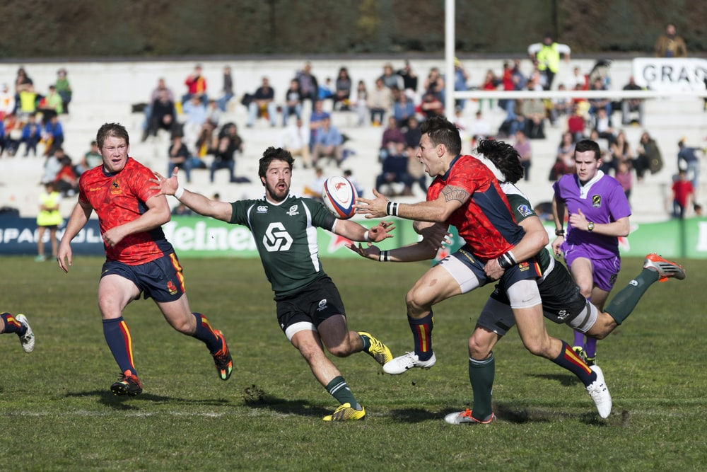 five men playing rugby during daytime
