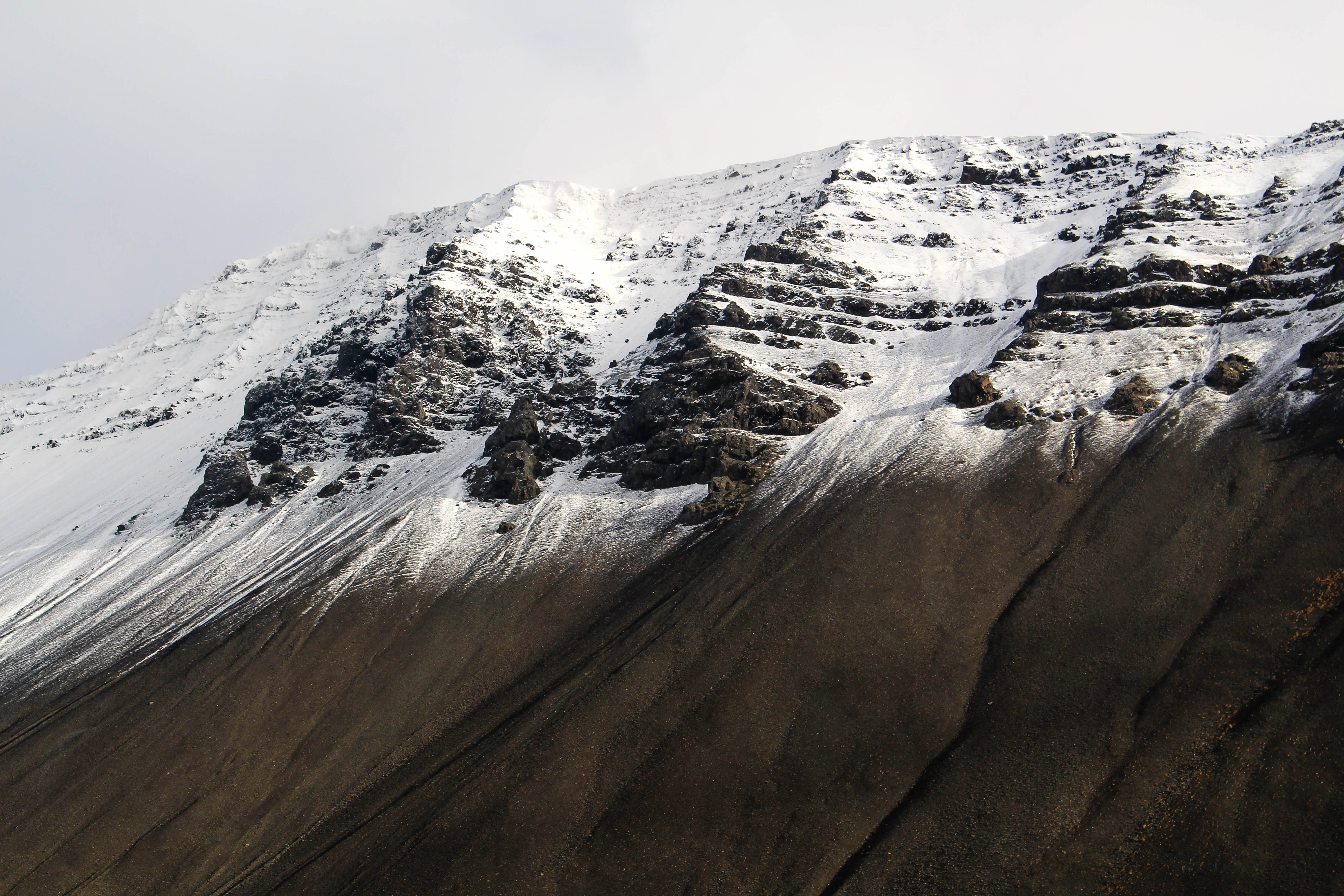 An eroded mountain slope covered in a snow blanket