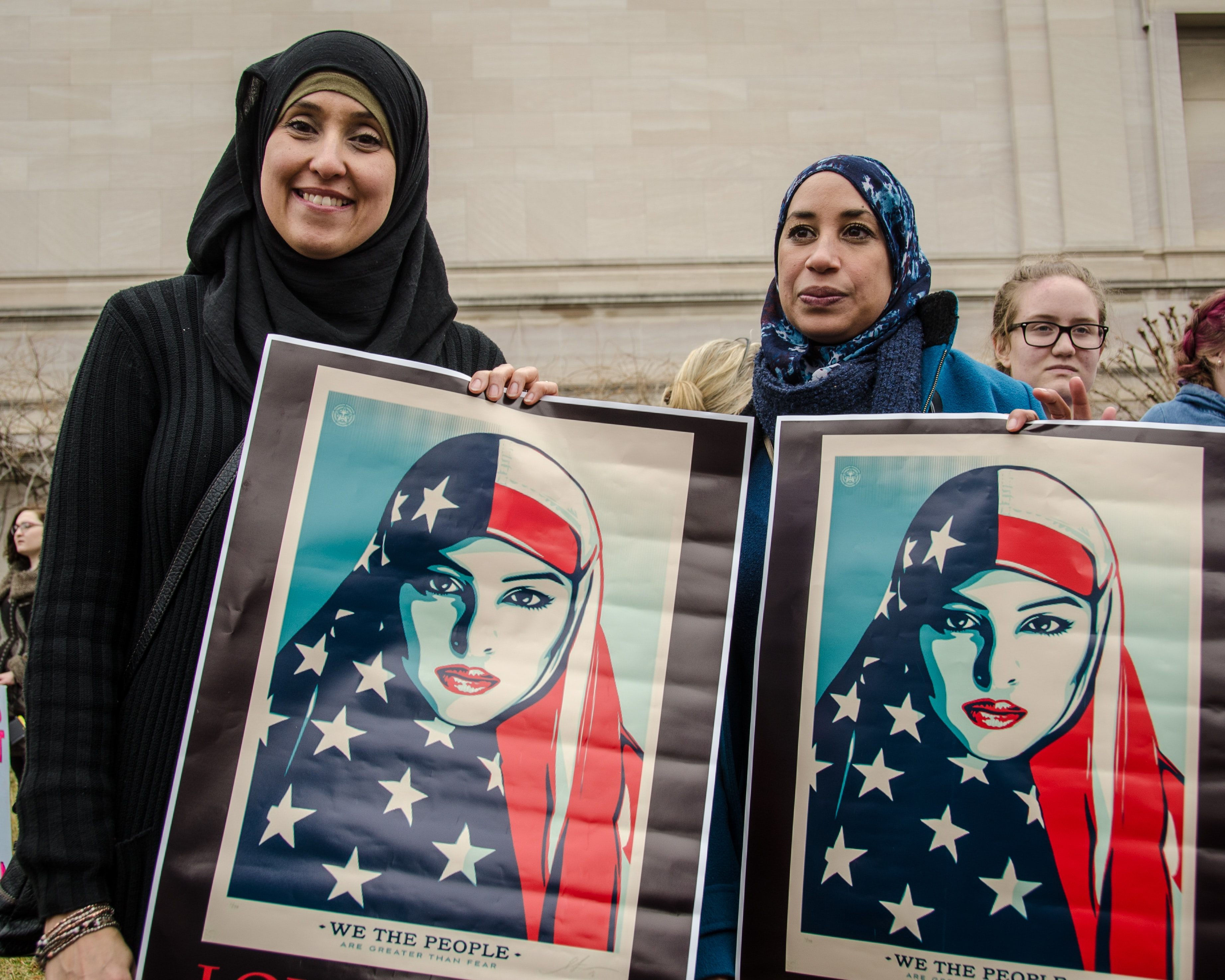 Two women in hijabs hold posters of an American Muslim woman at a march on Washington