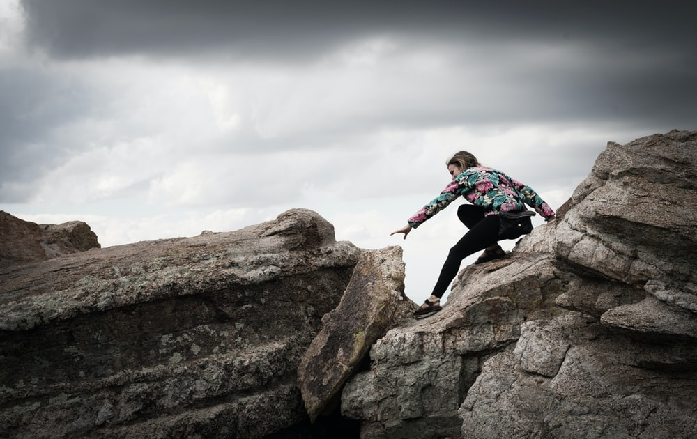 woman climbing on rocks during daytime photography