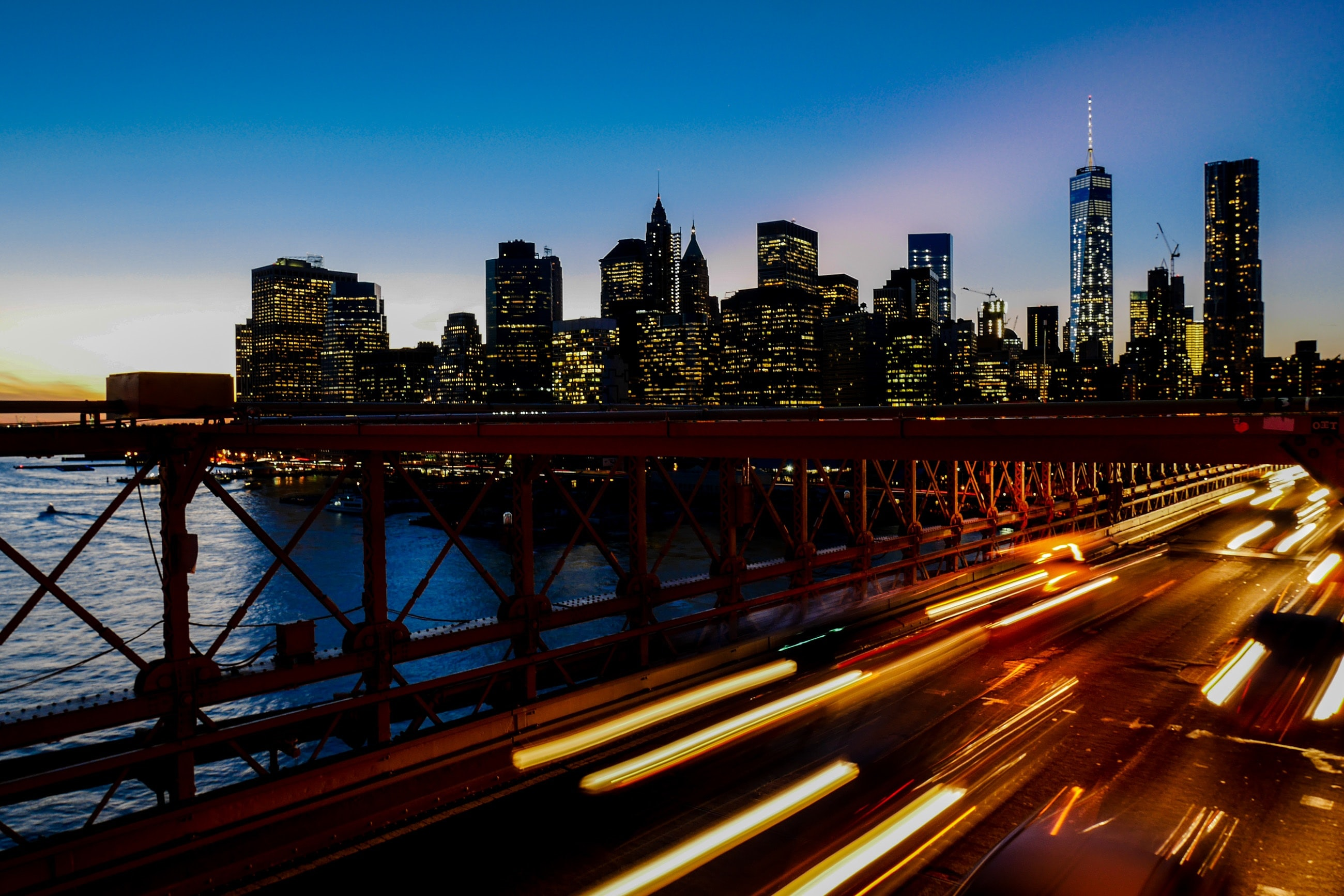 A long-exposure shot of light trails on the freeway with the New York city skyline at the back