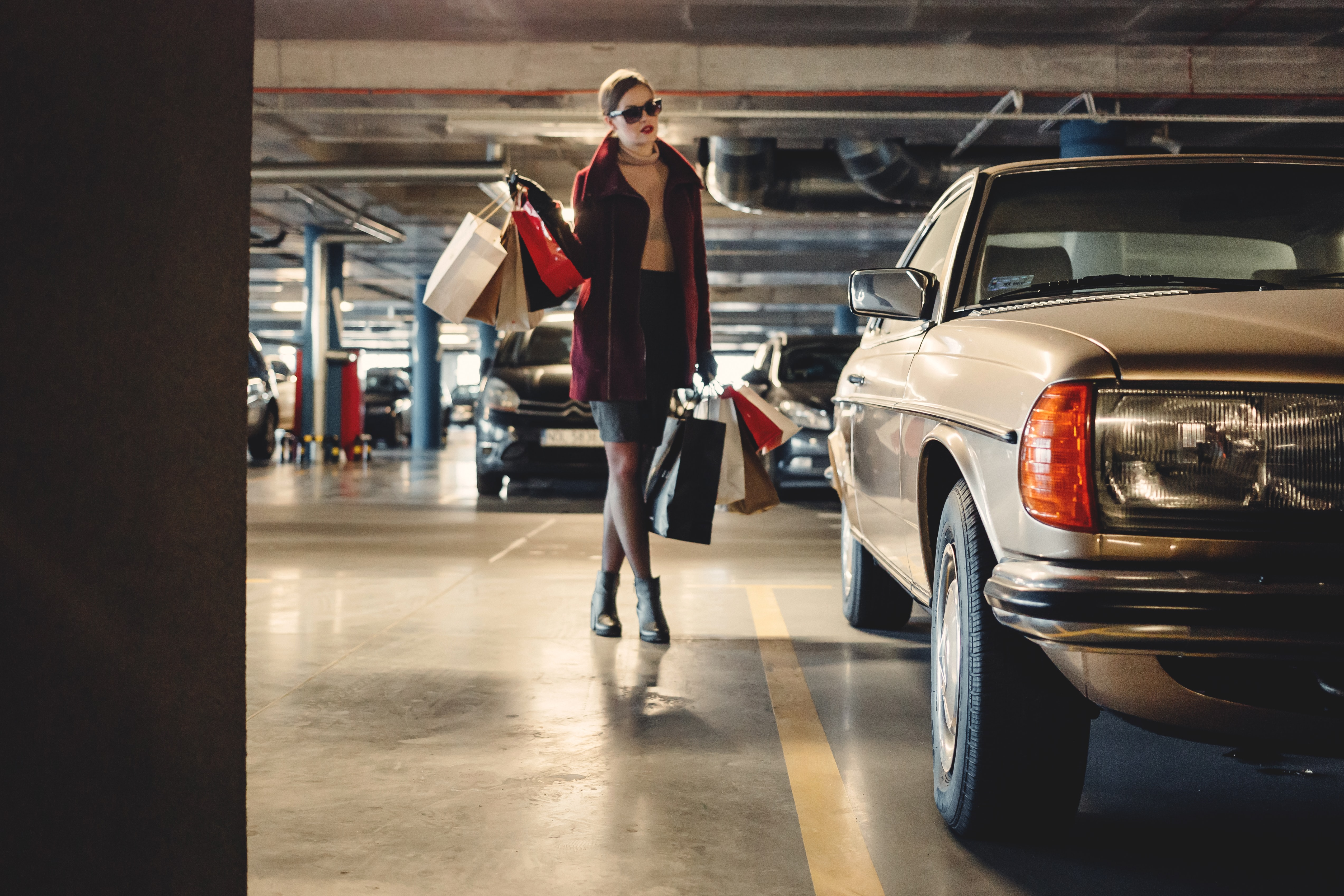 Woman with many shopping bags in sunglasses in a parking garage near a beige car