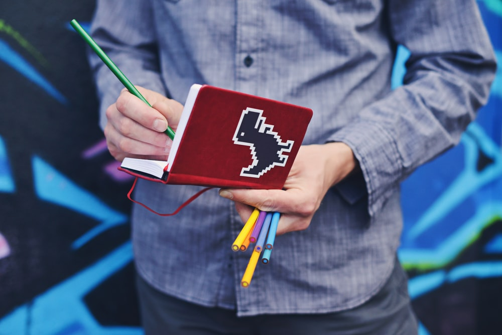 person in blue dress shirt holding red book and colored pens