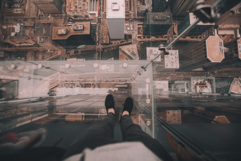 man standing on glass platform on top of building looking down on ground at daytime