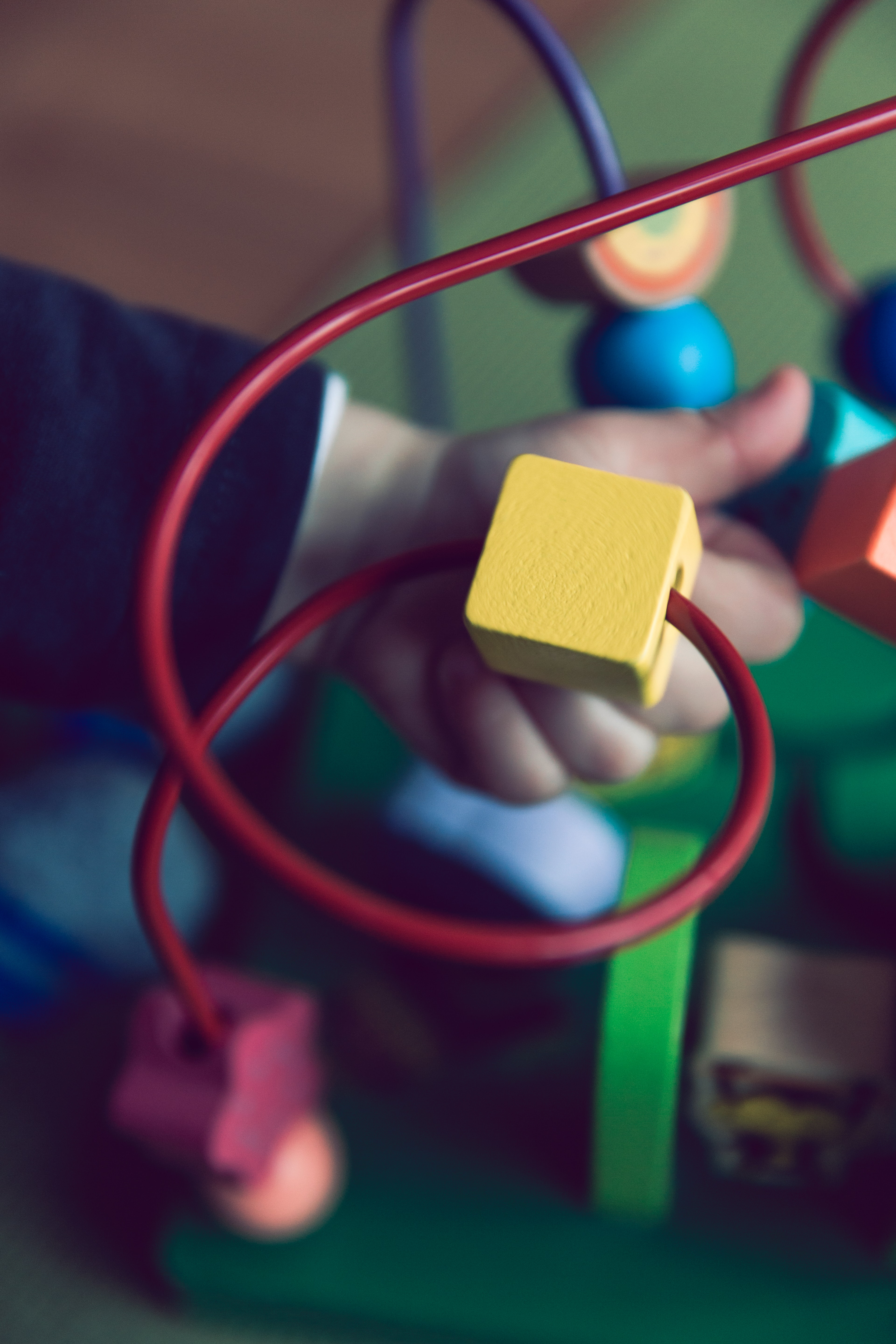 selective focus photo of baby playing activity cube