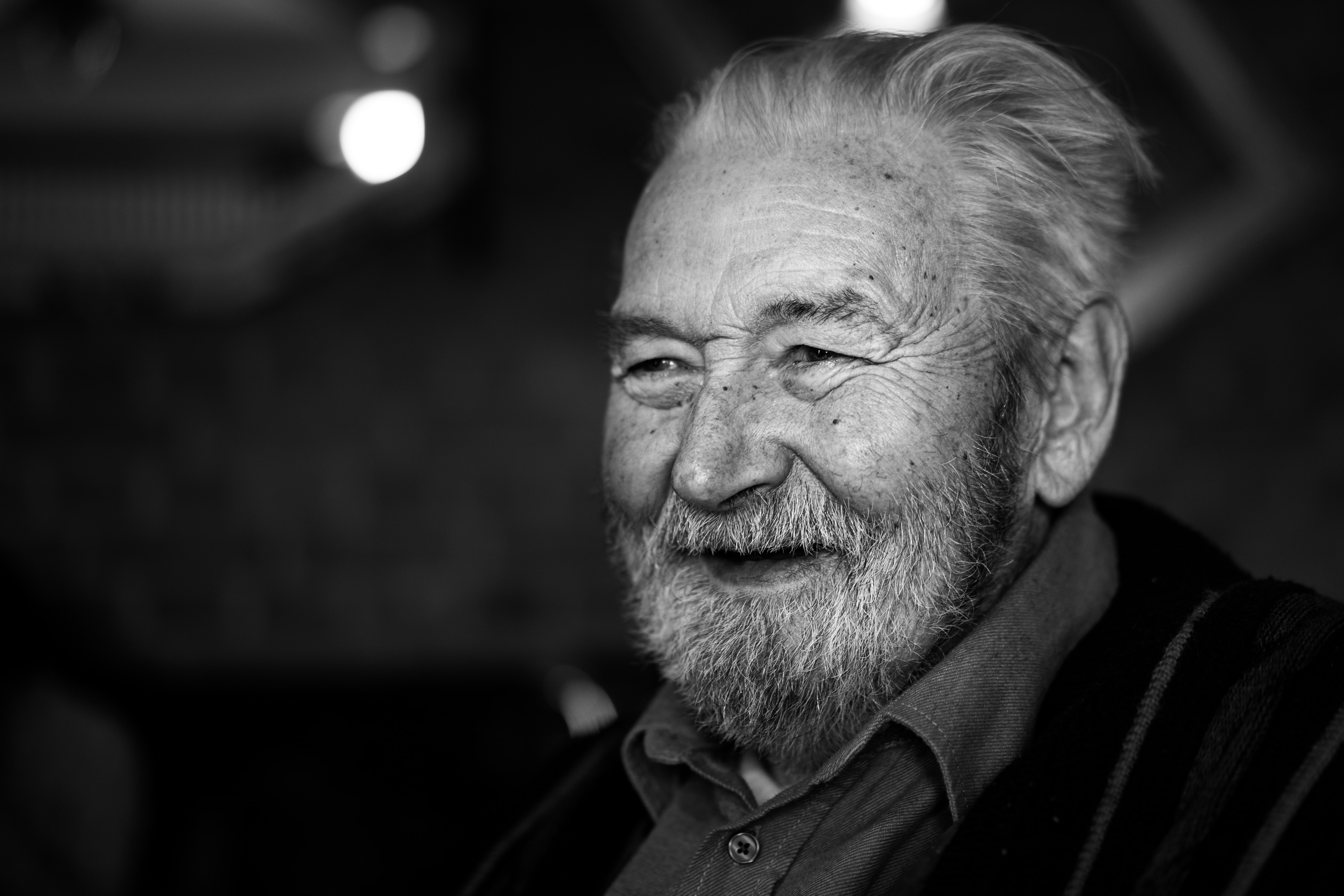 Black and white shot of old man with beard and grey hair smiling