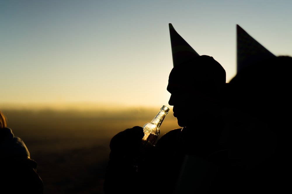 silhouette of person holding bottle during orange sunset