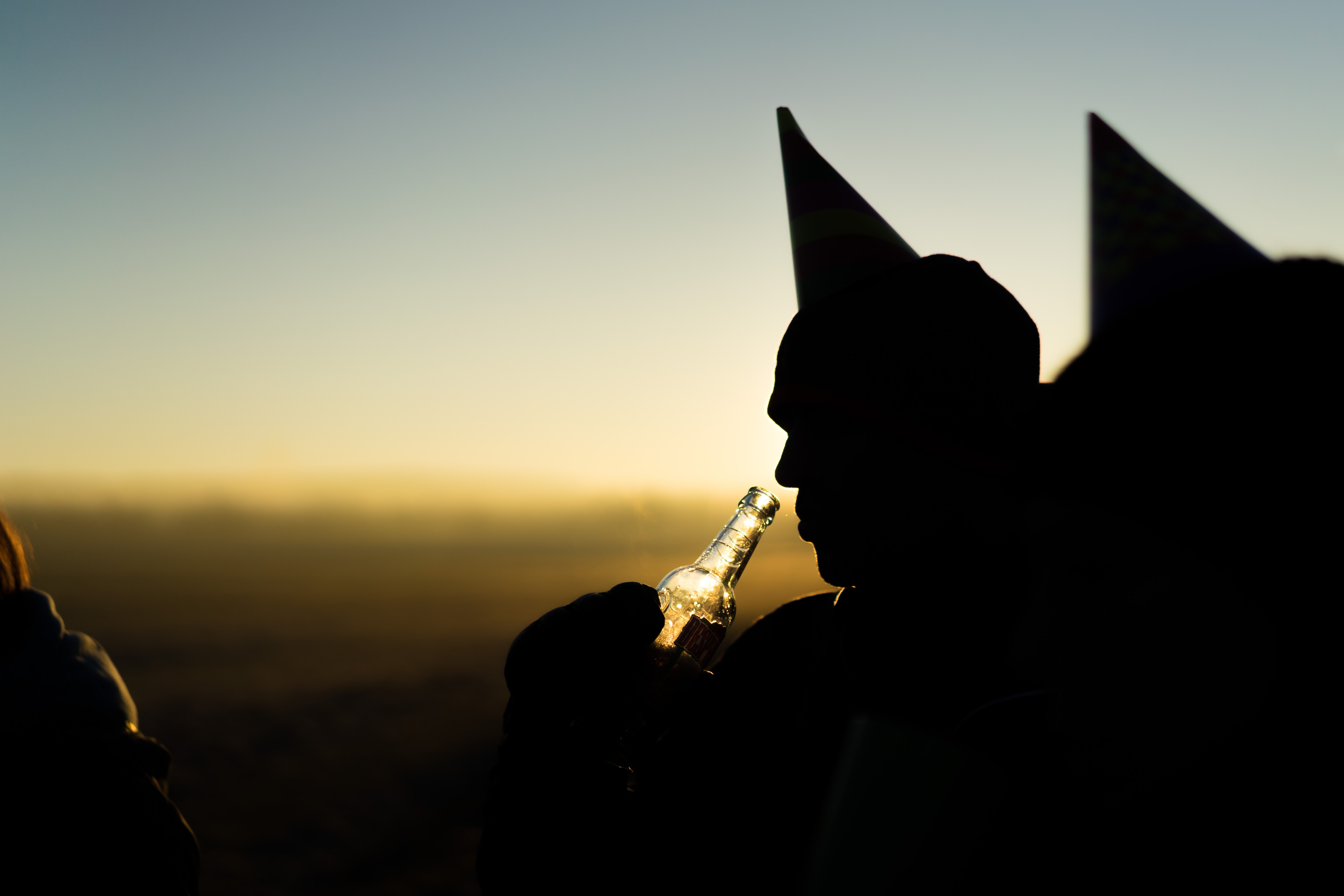 A silhouette of a man drinking from a beer bottle wearing a party hat