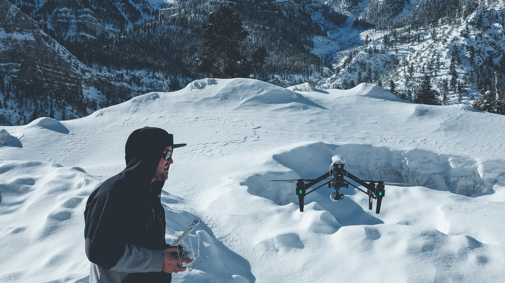 man in black hooded jacket controlling black drone