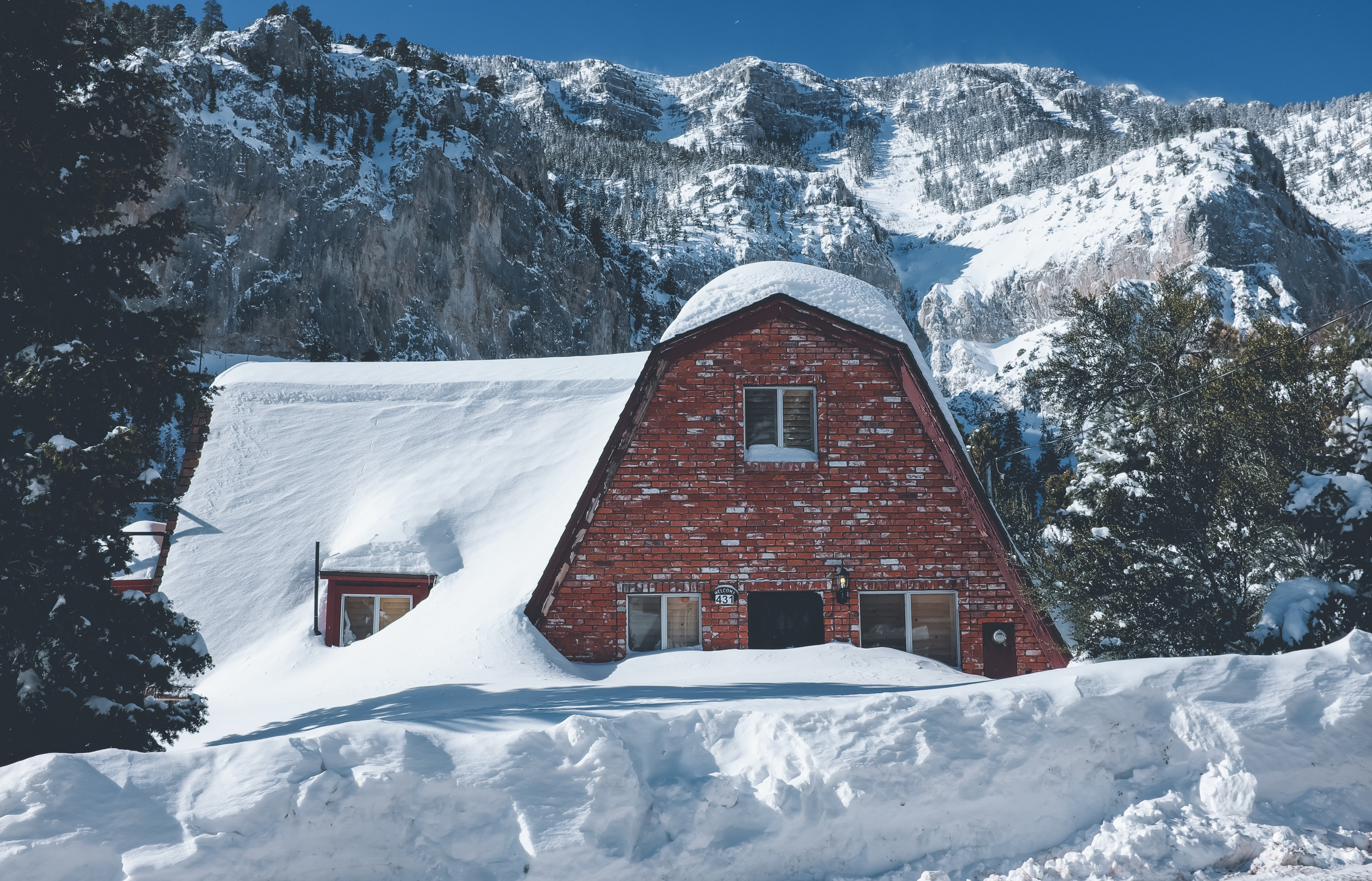 photo of brown brick house covered with snow
