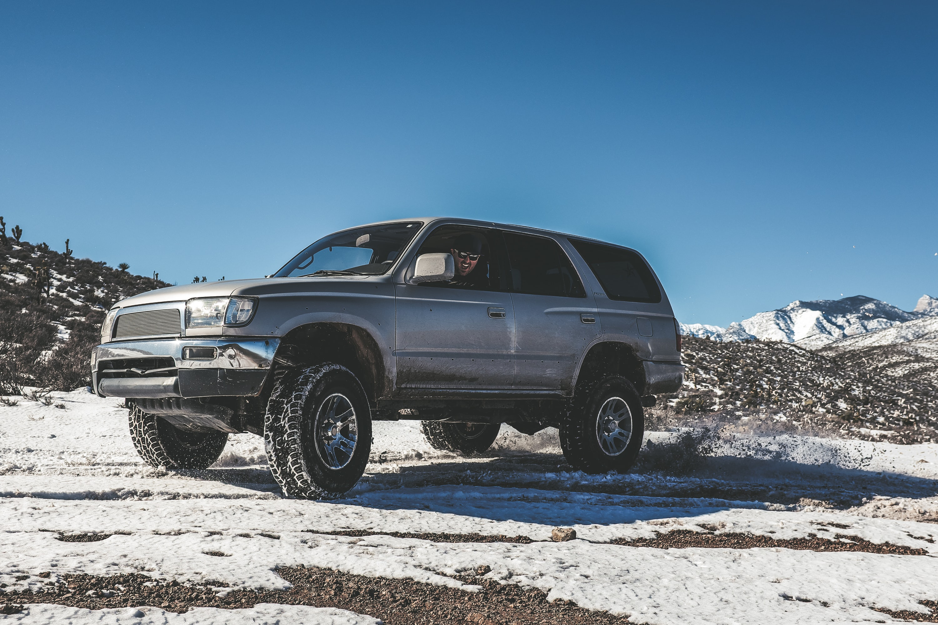 A 4x4 vehicle sitting in the snow on a hill at Mount Charleston