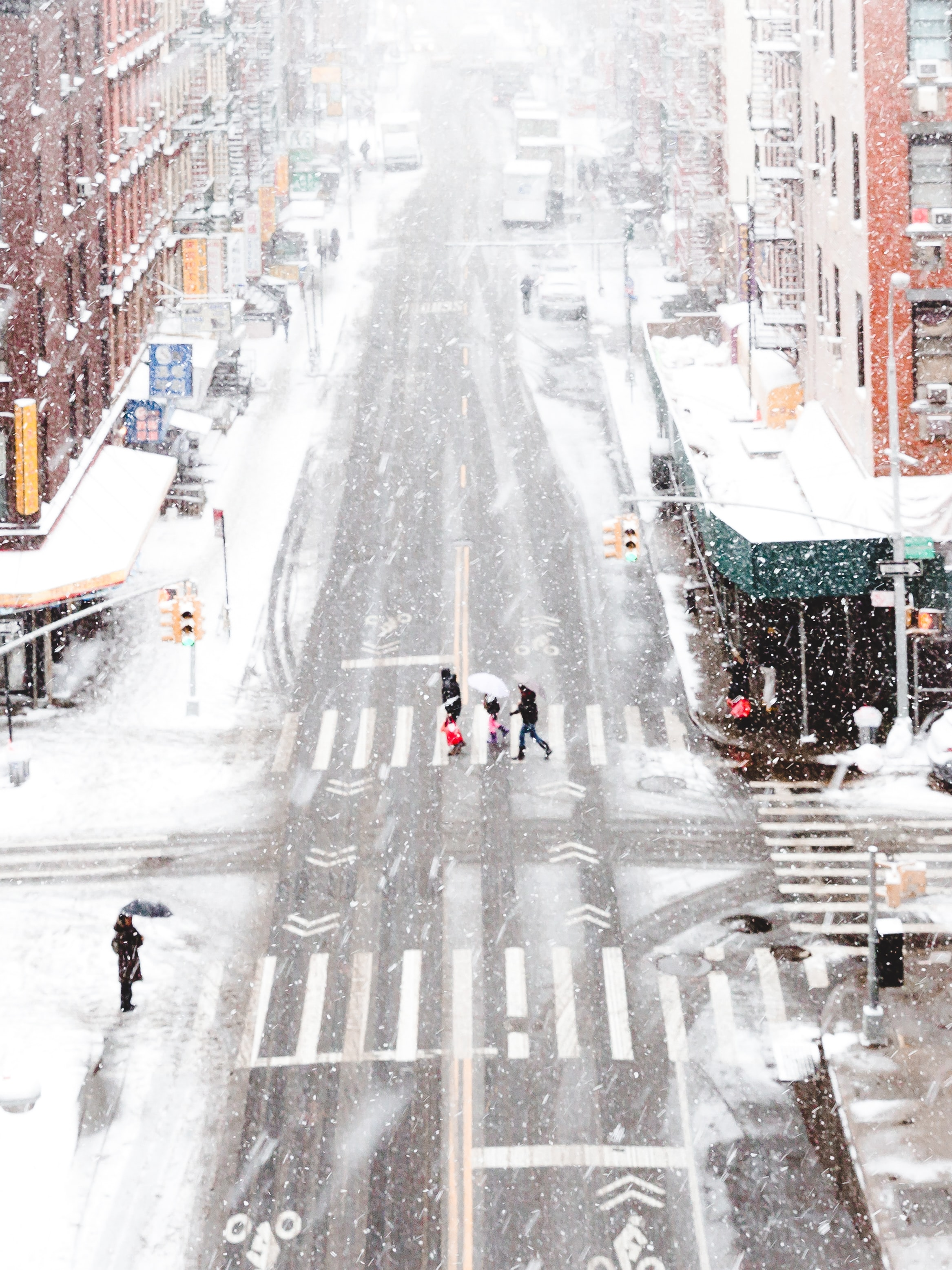People walking across the street at a crosswalk in Chinatown on a winter day