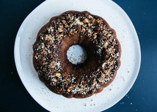 peanut sprinkled doughnut placed on round white ceramic saucer