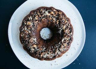 peanut sprinkled doughnut placed on round white ceramic saucer