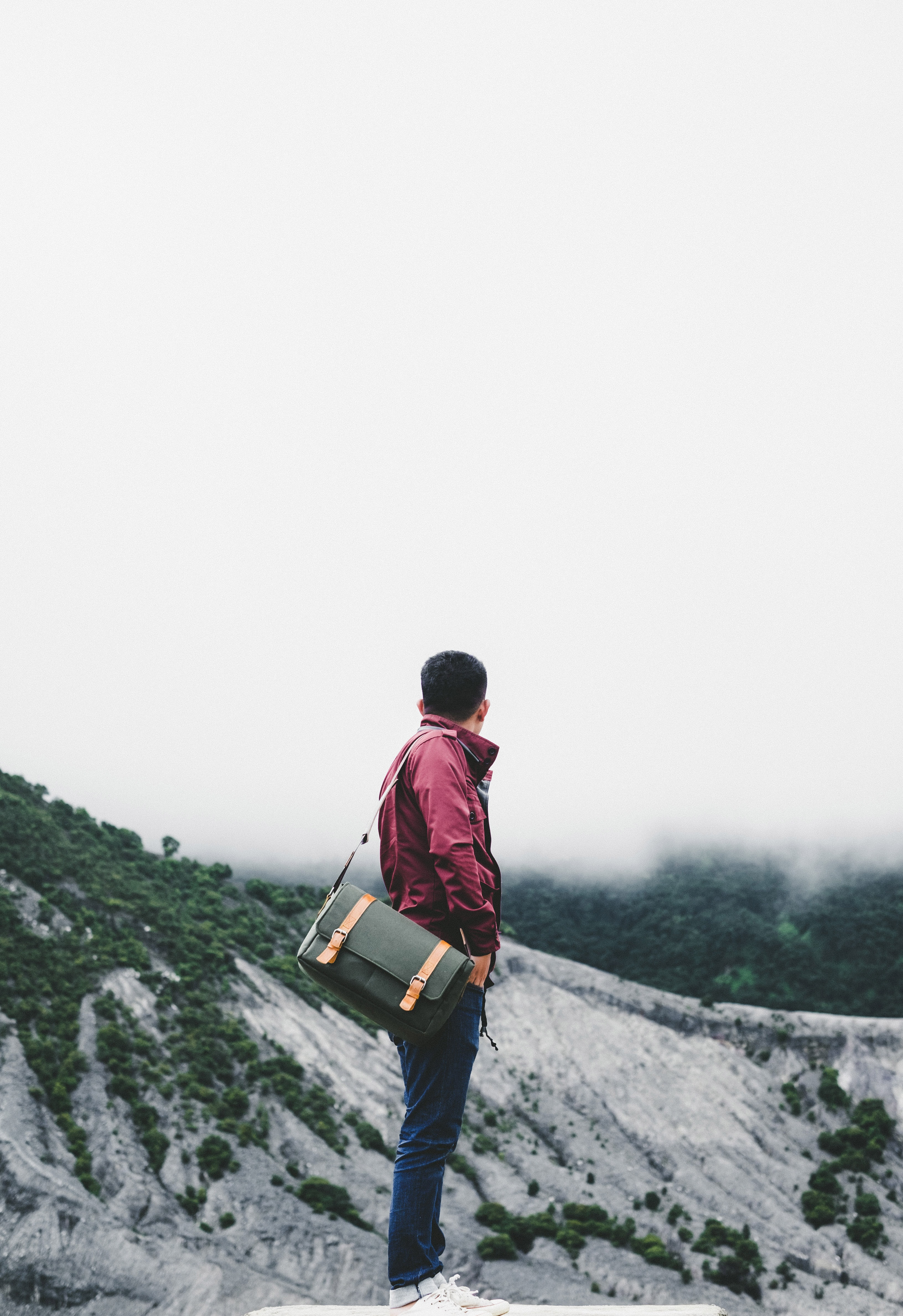 Stylish man dressed in jeans and red jacket with leather satchel standing in gray mountain terrain