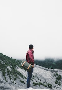 man carrying black crossbody bag while standing on platform overlooking hill under white sky at daytime