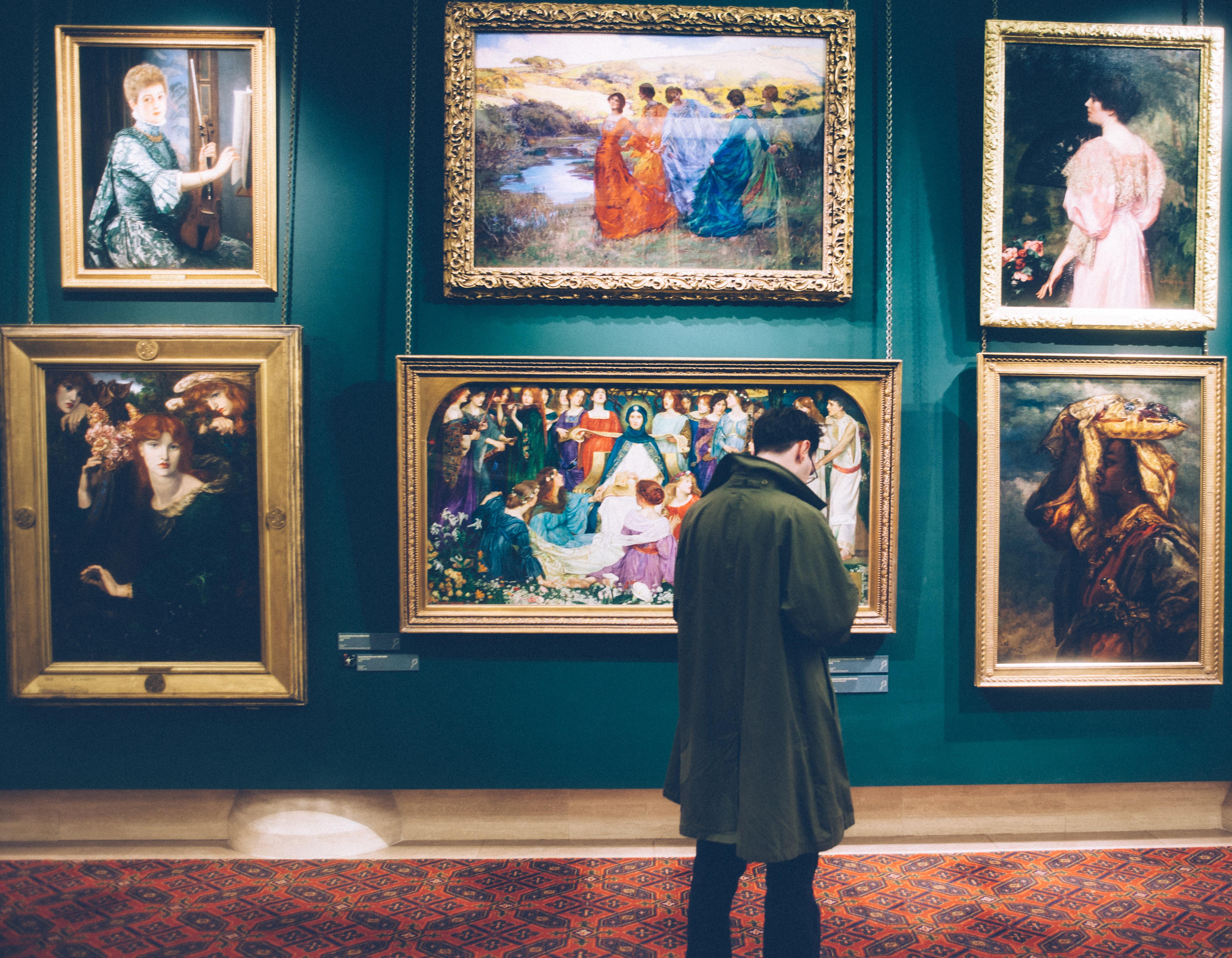 Man in long khaki jacket standing in art gallery browsing classic paintings